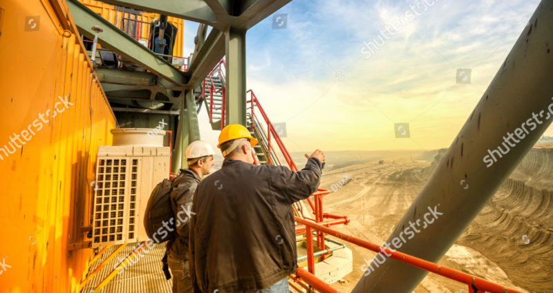 stock-photo-two-coal-mine-engineers-with-protective-helmets-standing-and-talking-on-a-huge-drill-machine-393097984