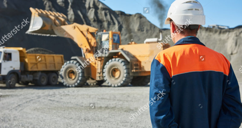 stock-photo-worker-engineer-looks-on-wheel-loader-loading-truck-492588217